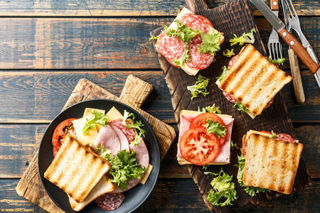 sandwiches with grilled toast ham salami cheese tomatoes and lettuce Banque d'images - 113696979