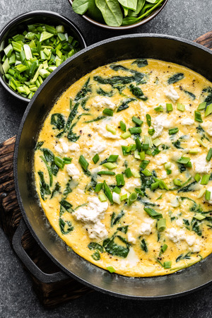 omelette with spinach and cheese in a pan on the concrete background top view Reklamní fotografie
