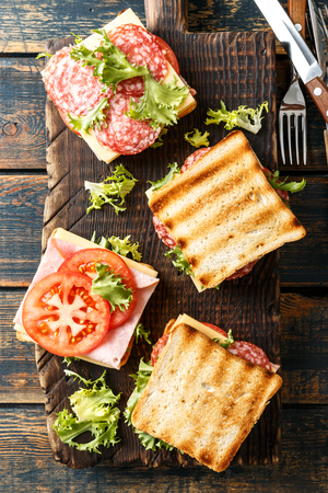 sandwiches with grilled toast ham salami cheese tomatoes and lettuce Stock Photo