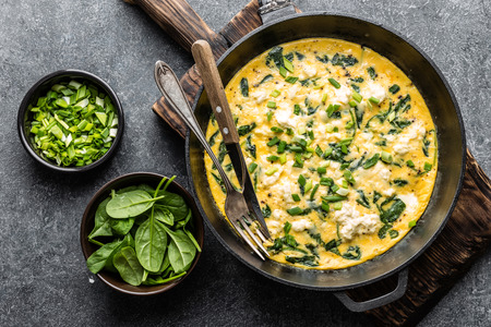 omelette with spinach and cheese in a pan on the concrete background top view Zdjęcie Seryjne
