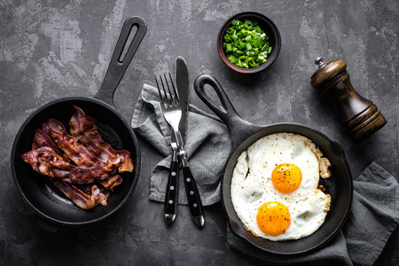 breakfast or brunch fried bacon and eggs in black skillets and top view