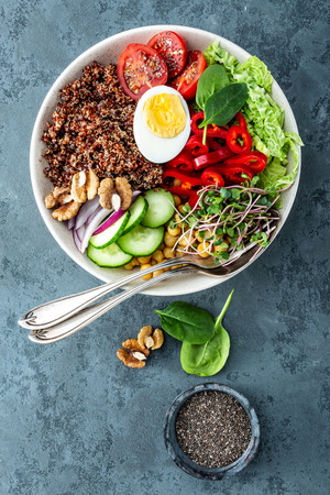 Healthy salad Buddha bowl dish of pepper, tomato, cucumber, chickpea, chia, sprouts, savoy and nuts. Healthy eating trend, superfood. Top view