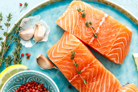 Seafood. Fresh raw salmon or trout fillets with ingredients top view