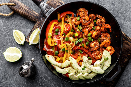 shrimp fajitas with bell pepper and onion cooked in a frying pan, top view