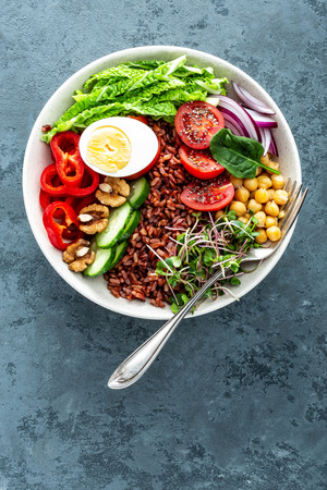 Healthy salad Buddha bowl dish of brown rice, pepper, tomato, cucumber, chickpea, chia, sprouts, savoy and nuts. Healthy eating trend, superfood. Top view Reklamní fotografie