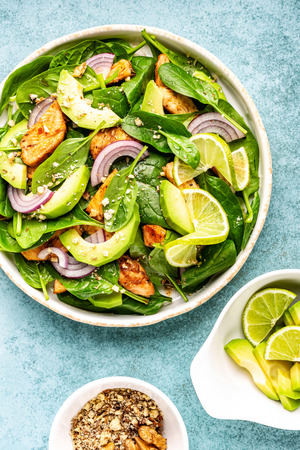 Healthy avocado salad with chicken breast and spinach, flat lay, top view