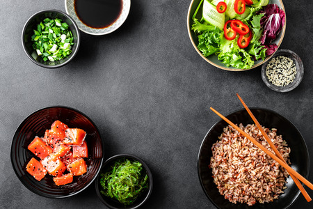culinary background of poke bowl ingredients - brown rice, trout or salmon fillet, Chuka Seaweed Salad, sesame and fresh vegetables, top view, copy space, healthy food background