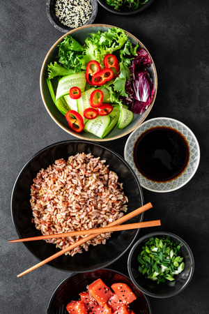 poke bowl ingredients - brown rice, trout or salmon fillet, Chuka Seaweed Salad, sesame and fresh vegetables, top view, healthy food trend Reklamní fotografie
