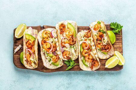 Tacos de camarones. Fajitas de mariscos con repollo, cebolla, perejil en tortillas servidas en tabla de cortar de madera