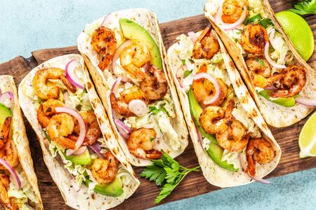 Shrimp tacos. Seafood fajitas with cabbage, onion, parsley in tortillas served on wooden cutting board