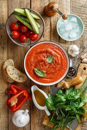 Gazpacho soup. Traditional spanish cold tomato soup of fresh raw vegetables with cooking ingredients on a wooden table top view Banque d'images