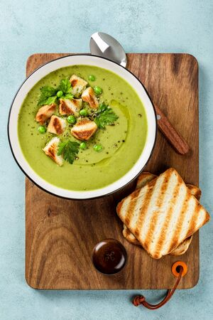 Pea soup. Green pea puree soup in a bowl served with grilled toasts, top view