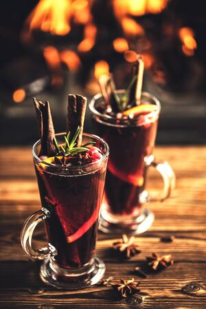 Mulled wine with spices in glasses on a wooden table against the background of a fireplace fire. Winter drink traditional for the Christmas holidays. 版權商用圖片