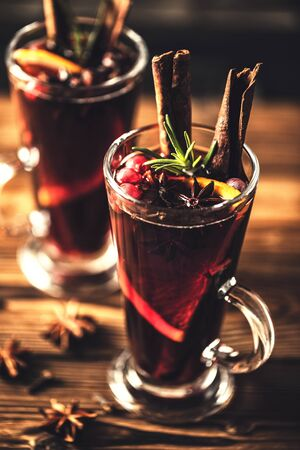 Mulled wine with spices in glasses on a rustic wooden table. Winter drink traditional for the Christmas holidays.