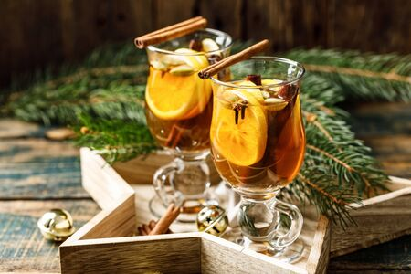Grog. Hot drink for the winter holidays of the New Year and Christmas. Spicy tea and rum cocktail with lemon, cardamom, cinnamon and cloves.