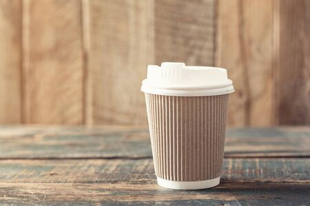 Coffee or tea in a paper cup with a lid