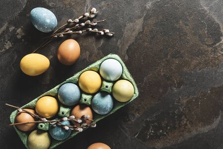 Easter background with space for a text. Natural dyed easter eggs on dark stone background.