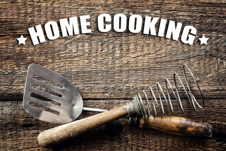 Slogan calling for home cooking on wooden background with kitchen utensils Imagens