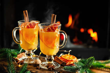 Mulled cider glasses on the background of fireplace fire. Hot mulled spiced apple cider cocktail for winter or autumn time.
