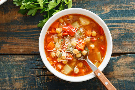 Vegetables soup bowl. Tuscan tomato chickpea soup with various vegetables, thyme and parmesan cheese. Imagens