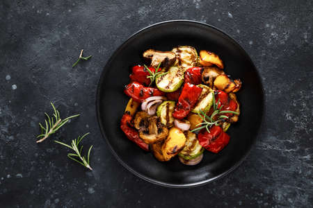 Grilled vegetables with mushrooms in a plate on a dark background