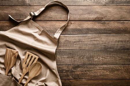 Culinary background, kitchen utensils and apron on kitchen countertop with blank space for any recipe or menu text Imagens
