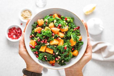 Vegetable salad bowl in woman hands. Fresh kale and baked pumpkin salad. Healthy eating concept Imagens