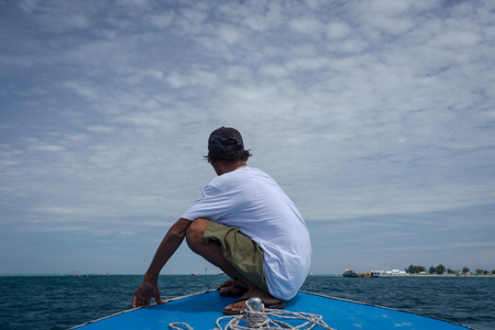 An old man sitting on the bow of the ship enjoying the beauty of the blue ocean. A local guide is guiding tourist on Harapan Island, Indonesia