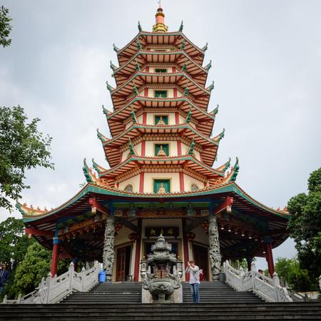 Semarang, Indonesia - December 3, 2017 : View of Pagoda Avalokitesvara at Vihara Buddhagaya Watugong with a man praying for his goodness. Vihara Buddhagaya is Buddhist temple located in Semarang, Indonesia. Pagoda Avalokitesvara is the tallest pagoda towe