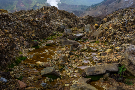 Rocky stream with brown water on a mountain. Beautiful landscape of mount Papandayan. Papandayan Mountain is one of the favorite place to hike on Garut.