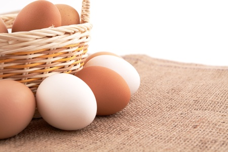 Eggs in a basket on sacking background photo