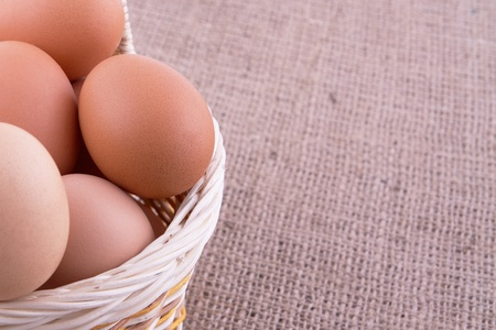 Eggs in a basket on sacking background Stock Photo - 13522250
