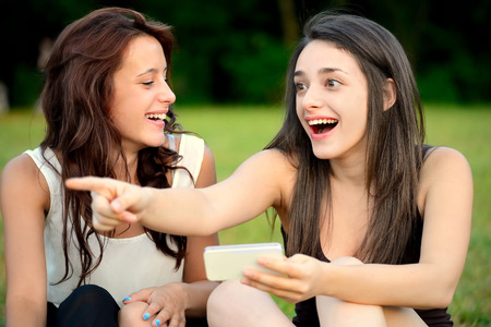 exhilarated: Two beautiful young women in a park one of them points at something with amazed face Stock Photo