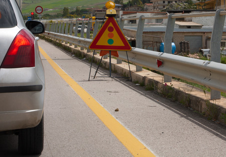 red traffic light: a car is stopping at the red traffic light during some work in progress on a road in sicily