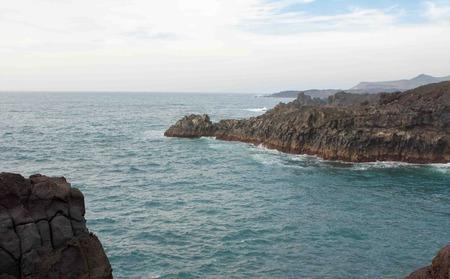 los hervideros: a cloudy sky over los hervideros rough cliff view