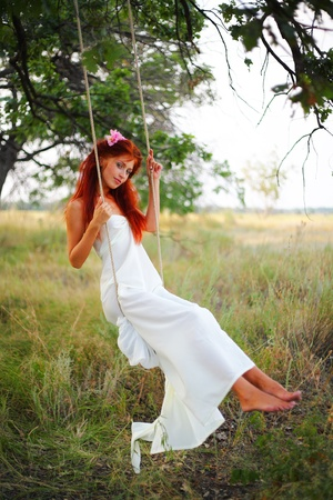 swing: The red-haired girl in a white dress shakes on a swing in a grove