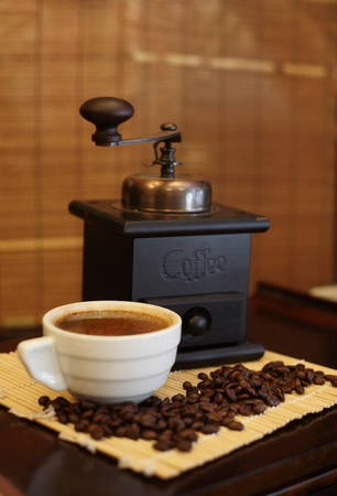Coffee grinder, white cup of coffee and grains of fried coffee on a mat, Shallow depth-of-field