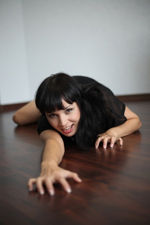 The brunette on a parquet in a pose of a panther