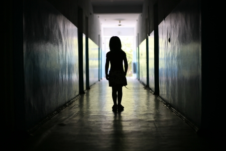 Silhouette of the little girl in a long corridor
