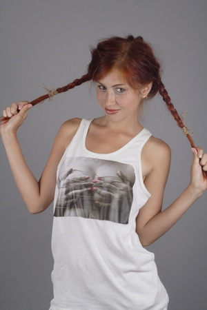 furtive: The red-haired girl in a white vest behaves for plaits Stock Photo