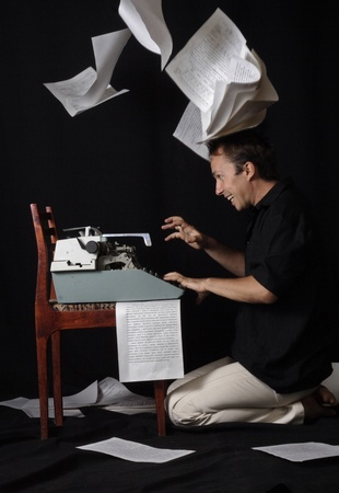 The writer selflessly prints on the typewriter, and sheets around fly Stock Photo