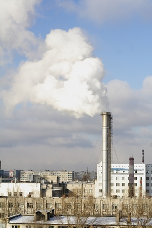 Industrial landscape with houses and a smoking pipe Stock Photo