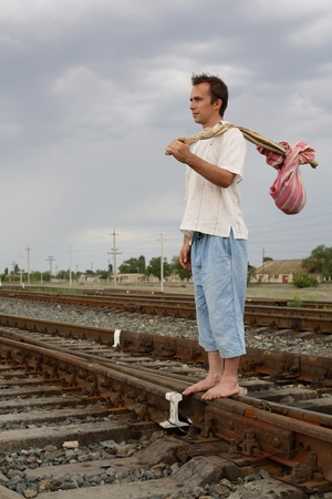 The person with a bag costs on rails and looks afar Stock Photo