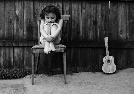 The small sad girl sits on a chair near to a guitar Stock Photo