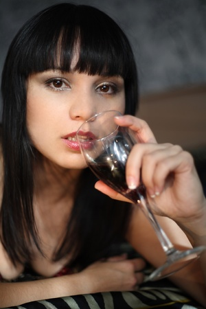 The woman holds a glass with wine near lips. (Small depth of sharpness) Stock Photo
