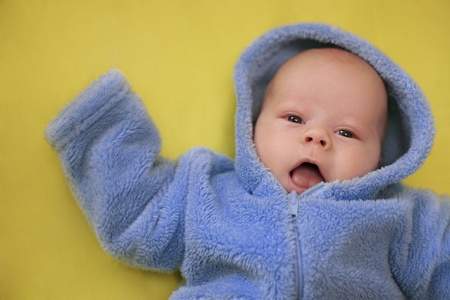 The cheerful baby in blue overalls on a yellow background (Small depth of sharpness) Stock Photo