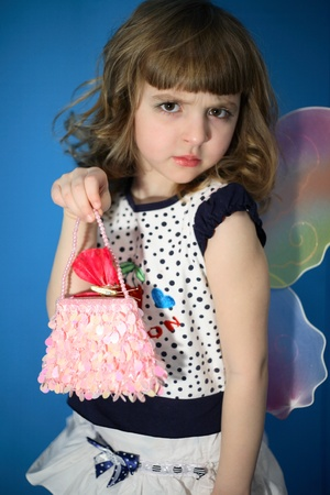 Portrait of the sad girl with wings and a handbag on dark blue