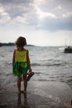 The lonely girl costs on a pier and looks at a heavy sea