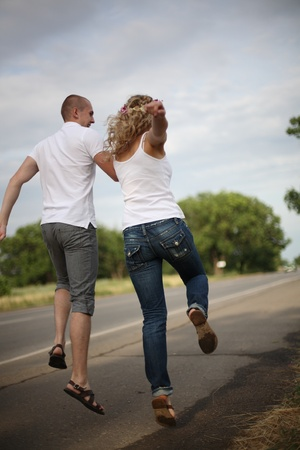 The guy and the girl go on highway, having joined hands photo