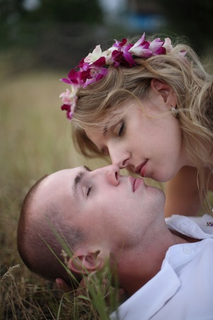 The girl kisses softly the guy lying on a grass